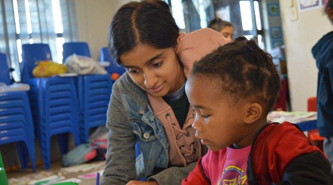 A teenager helps a child with a literacy exercise as part of her volunteer work abroad
